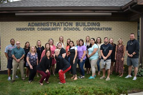 twelve teachers in front of a building
