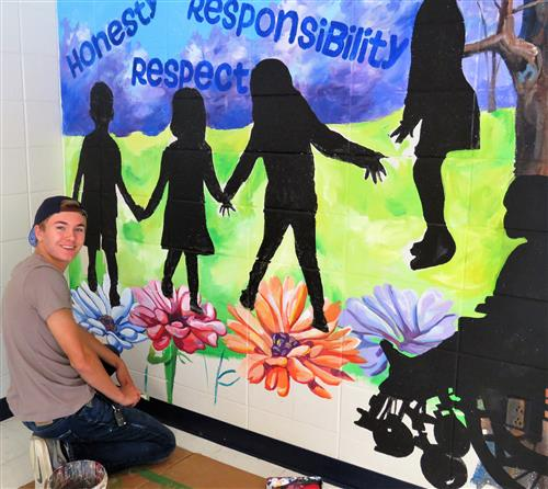young man painting children and flowers on wall