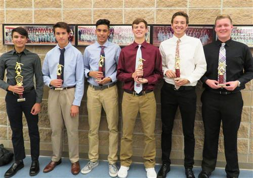 Picture of six boys soccer players with trophies