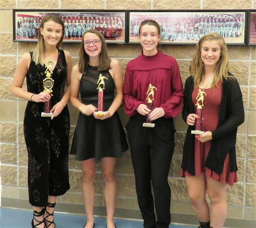 Picture of 4 girls soccer players with trophies