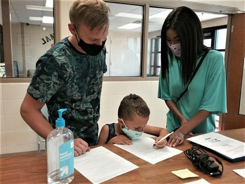 little boy signing documents while parents watch
