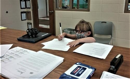 little girl with mask signing a document