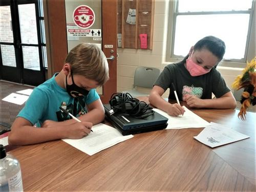 boy and girl signing documents