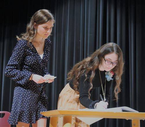 girl signing book while another one watches