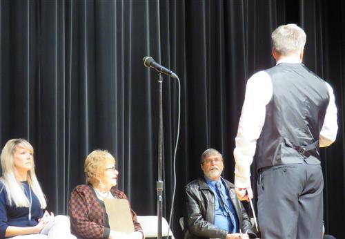 man talking to men and women on a stage